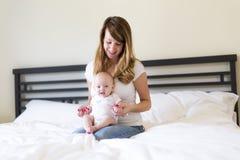Porträt der Mutter mit ihrem Baby des dreimonatigen Babys im Schlafzimmer stockbild