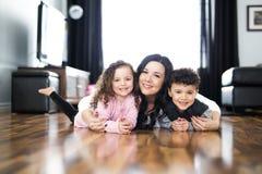 Porträt der Mutter mit ihren zwei Kindern zu Hause stockbilder