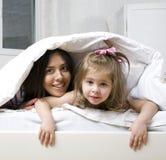 Porträt der Mutter und der Tochter, die in Bett und im Lächeln legen stockfotos