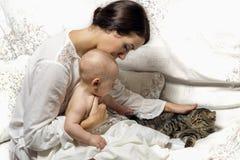 Porträt der Mutter und des Babys, das ein Kätzchen strich Haupt-atmosp Lizenzfreie Stockfotos