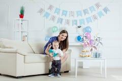 Porträt der Mutter und des Babys mit Geburtstagskuchen Lizenzfreies Stockbild