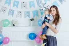 Porträt der Mutter und des Babys mit Geburtstagskuchen Stockfotos