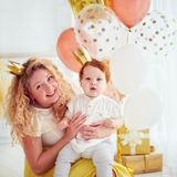 Porträt der Mutter und des netten kleinen Babys auf seiner 1. Geburtstagsfeier stockbild