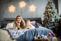 Porträt der Mutter und des Sohns auf neues Jahr ` s Hintergrund lizenzfreies stockbild