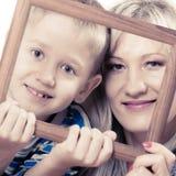Porträt der Mutter und des Sohns, die Fotorahmen halten Lizenzfreies Stockfoto