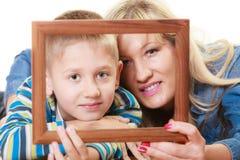 Porträt der Mutter und des Sohns, die Fotorahmen halten Lizenzfreie Stockfotos