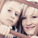 Porträt der Mutter und des Sohns, die Fotorahmen halten Lizenzfreies Stockbild