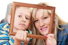 Porträt der Mutter und des Sohns, die Fotorahmen halten Stockfotos