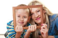 Porträt der Mutter und des Sohns, die Fotorahmen halten Stockbild
