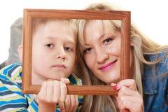 Porträt der Mutter und des Sohns, die Fotorahmen halten Lizenzfreie Stockbilder