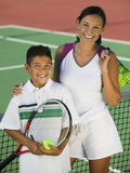 Porträt der Mutter und des Sohns durch Netz auf Tennisplatz Lizenzfreie Stockfotos