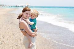 Porträt der Mutter und ihres kleinen Sohns auf dem Strand Lizenzfreies Stockbild