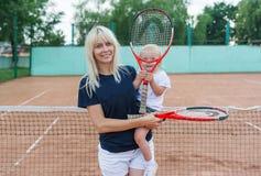 Porträt der Mutter und der kleinen Tochter auf dem Tennisplatz Lizenzfreies Stockfoto