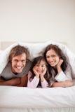 Porträt der Muttergesellschaft, die unter einem Duvet mit ihrer Tochter liegen stockbild