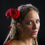 Porträt der nassen Frau mit roten Rosen im Haar Lizenzfreie Stockbilder