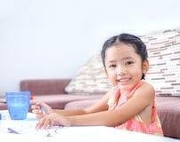 Porträt der netten asiatischen thailändischen Malerei des kleinen Mädchens die Farbe an ho Lizenzfreie Stockfotografie