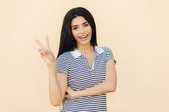 Porträt der netten Brunettefrau mit frohem Ausdruck, macht Friedenszeichen mit zwei Fingern, zufällig gekleidet, lokalisiert über lizenzfreies stockbild