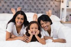 Porträt der netten Familie von mehreren Generationen, die auf Bett liegt Lizenzfreie Stockfotos