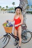 Porträt der netten Frau kleidete im modischen roten Badeanzug an, der mit Retro- Fahrrad auf dem Strand steht Stockfotografie