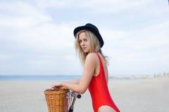 Porträt der netten Frau kleidete im modischen roten Badeanzug an, der mit Retro- Fahrrad auf dem Strand steht Stockfoto