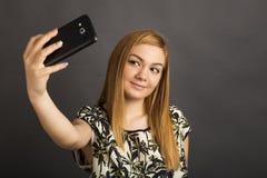 Porträt der netten Jugendlichen selfie mit ihrem intelligenten Telefon nehmend Lizenzfreie Stockbilder