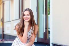 Porträt der netten jungen draußen sitzenden und lächelnden Frau stockbild