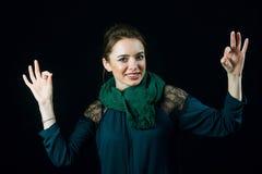 Porträt der netten jungen Frau, die Gestenbrunnen zeigt lizenzfreie stockbilder