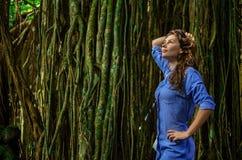 Porträt der netten jungen Frau macht Foto im Dschungel mit lians Das Mädchen steht den Baum neben ihr bereit E stockfotos
