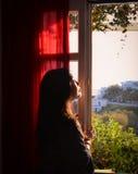 Porträt der netten jungen Frau schaut heraus Fenster Lizenzfreies Stockfoto