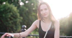 Porträt der netten lächelnden jungen Frau mit Fahrrad auf einer Stadtstraße Lizenzfreie Stockfotografie