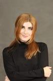 Porträt der netten roten jungen Frau auf einem grauen Hintergrund Stockfotos