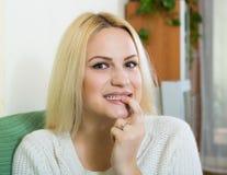 Porträt der positiven Frau mit dem Finger über Lippen Lizenzfreies Stockbild