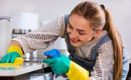 Porträt der positiven Hausfraureinigung in der Küche Lizenzfreie Stockbilder
