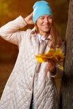 Porträt der positiven jungen Frau mit Herbstlaub Lizenzfreies Stockfoto