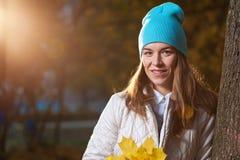 Porträt der positiven jungen Frau mit Herbstlaub Lizenzfreie Stockfotos