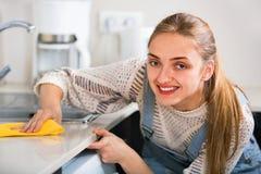 Porträt der positiven jungen Hausfraureinigung mit Versorgungen Lizenzfreie Stockfotografie