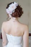 Porträt der Rückseite der Braut im weißen Kleid mit Frisur und flo Lizenzfreies Stockbild