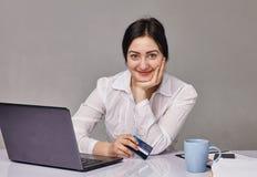 Porträt der recht jungen Frau, die im Büro arbeitet Lizenzfreie Stockfotos
