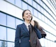 Porträt der recht jungen Geschäftsfrau, die am Telefon nahe Gebäude spricht Stockbilder