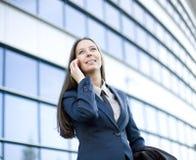 Porträt der recht jungen Geschäftsfrau, die am Telefon nahe Gebäude spricht Lizenzfreie Stockbilder