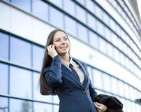 Porträt der recht jungen Geschäftsfrau, die am Telefon nahe Gebäude spricht Stockfotografie