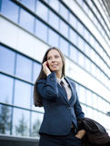 Porträt der recht jungen Geschäftsfrau, die am Telefon nahe Gebäude spricht Lizenzfreies Stockfoto