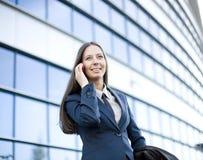 Porträt der recht jungen Geschäftsfrau, die am Telefon nahe Gebäude spricht Lizenzfreies Stockbild