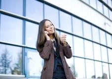 Porträt der recht jungen Geschäftsfrau, die am Telefon nahe Gebäude spricht Stockbild