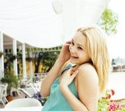 Porträt der recht modernen Freundin bei dem Caféfreilicht-Innentrinken und der Unterhaltung am Telefon lächelnd, Chat habend und Stockbilder