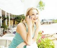 Porträt der recht modernen Freundin bei dem Caféfreilicht-Innentrinken und der Unterhaltung am Telefon lächelnd, Chat habend und Lizenzfreies Stockfoto
