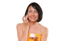 Porträt der recht reifen Frau, die Gesichtscreme verwendet Lizenzfreie Stockbilder