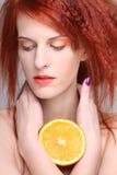 Porträt der redhaired Frau mit orange Hälfte Stockfotos
