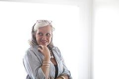 Porträt der reifen Frau durch ein Fenster Lizenzfreie Stockbilder