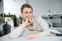 Porträt der reifen Frau entspannend auf Sofa Lizenzfreie Stockfotografie